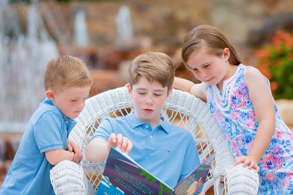 big brother reads book to little brother during photo session