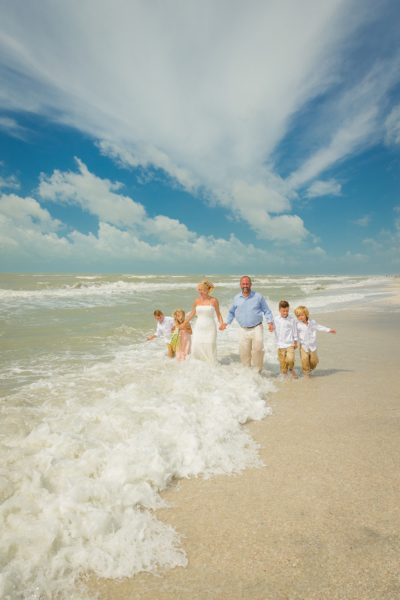 family walks along Sanibel beach