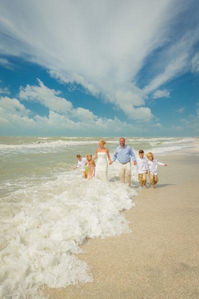 family walks along Sanibel beach