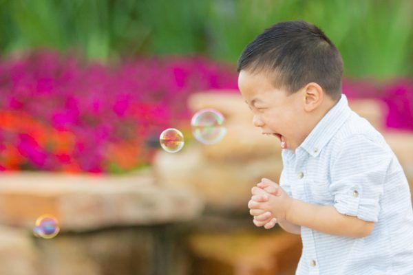 photo of boy and bubbles on beach