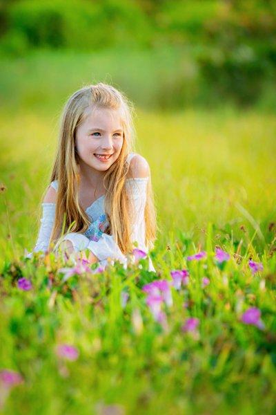 girl poses for picture in flower garden