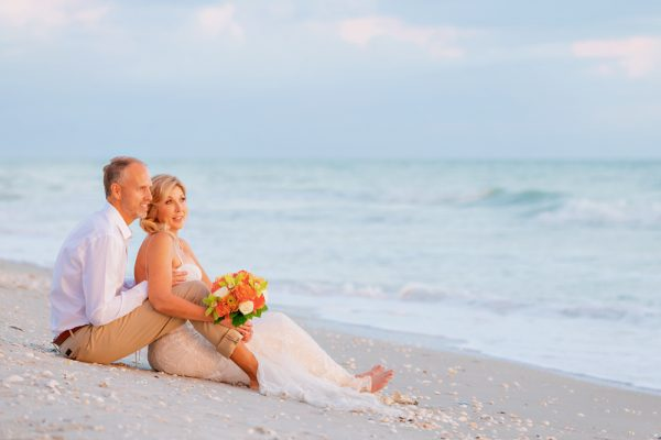 wedding couple sit on beach