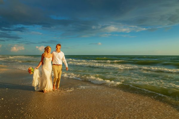 wedding couple walk on beach