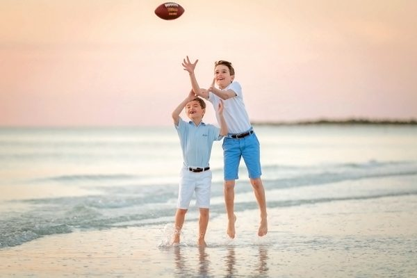 two brothers playing football on Marco Island beach