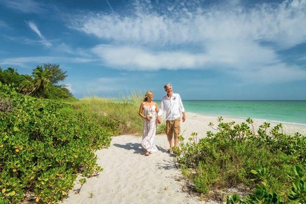 couple walk on Sanibel beach after ceremony